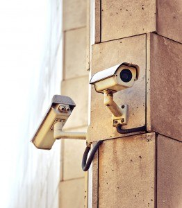 Security CCTV camera mounted on the building wall as apart of private property protection system or Big Brother Concept with white copy space