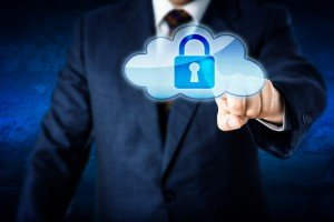 Upper body of a business man reaching out to touch a locked cloud computing icon. Metaphor for information security and protection in cyber space. Corporate suit and blue wall in background. Close up.