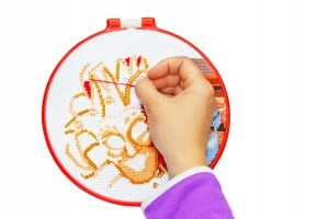 A man's hand embroidering a cross pattern on the hoop ( isolate over white background )
