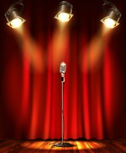 Stage with red curtians, microphone and spotlight.