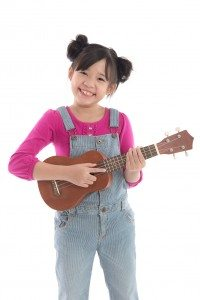 Cute asian girl holding ukulele on white background isolated