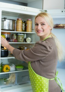 Happy blonde woman looking for something in refrigerator in home